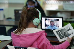 (Eric Gay | AP file photo) Students in San Antonio attend a class in-person as they interact with classmates virtually on Feb. 8, 2021. Sen. Mitt Romney is pushing for schools to reopen in-person classes, and even wants it as a requirement for new pandemic aid to them.