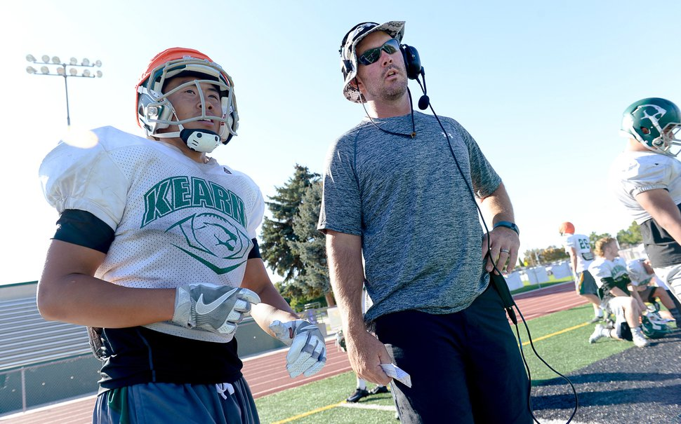 (Francisco Kjolseth | The Salt Lake Tribune) Kearns football coach Matt Rickards works with wide receiver Peter Do during practice on Wednesday, Sept. 7, 2016. Coaches across the state, including Rickards, are vehemently criticizing a proposal to eliminate restrictions on prep athletes transferring between schools, saying it would create a free-for-all that encourages athletes to focus on winning and entitlement, rather than than character development and overcoming adversity.