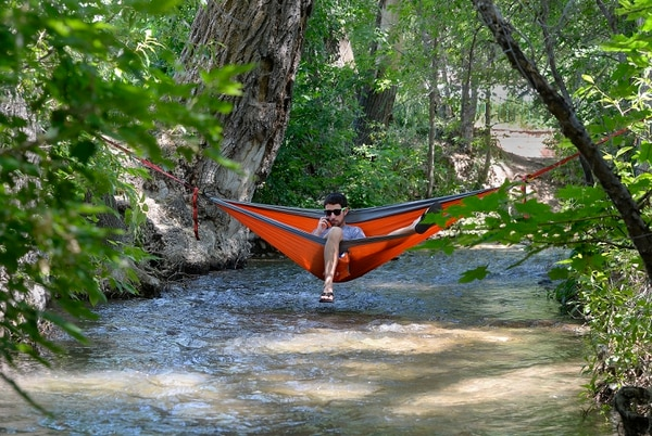 Al Hartmann | The Salt LakeTribune Man who wished to be unidentified finds some peace from the crowds and coolness from the 100 degree heat July 4th stretched across Parley's Creek in his hammock in Sugarhouse Park.