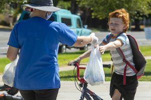 (Rick Egan  |  The Salt Lake Tribune)     Shayla Steinfels delivers lunches to student at Rose Park Elementary on Friday, Aug. 7, 2020.