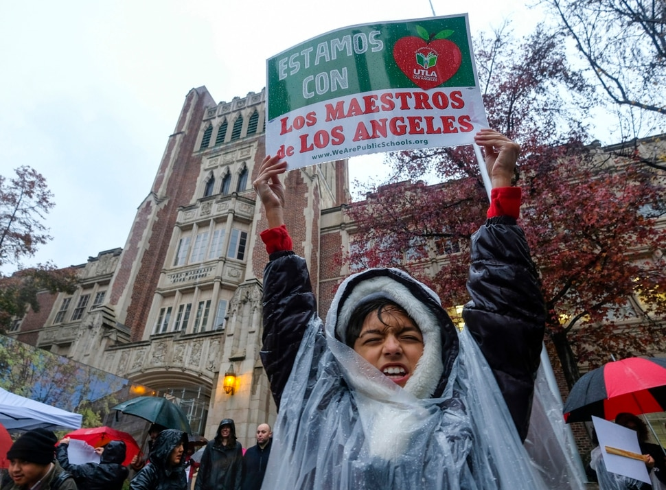 (Ringo H.W. Chiu | The Associated Press) Alessandro Niculescu, 10, holds up a sign in the rain during a teacher strike outside John Marshall High School, Monday, Jan. 14, 2019, in Los Angeles. Tens of thousands of Los Angeles teachers are striking after contentious contract negotiations failed in the nation's second-largest school district.