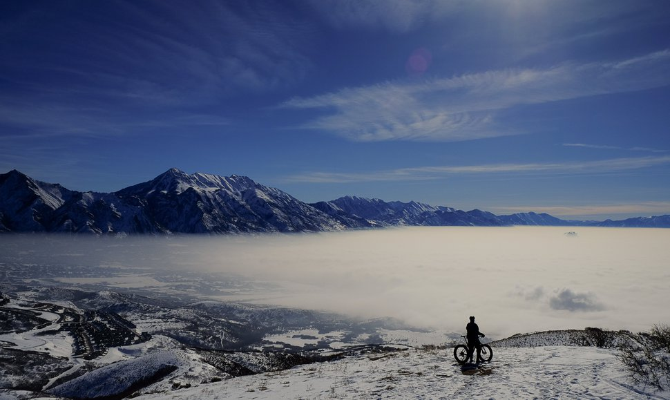 Francisco Kjolseth | The Salt Lake Tribune Jason Dunn of Draper seeks higher, cleaner air as he rides his bike to a peak overlooking the obscured Utah county as air quality continues to deteriorate with inversion conditions trapping cold air on Friday, Feb. 12, 2016.
