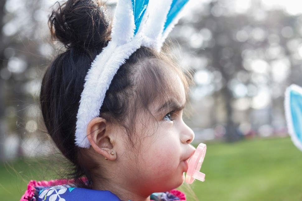 (Nicole Boliaux | For The Tribune) Perla Ramirez dons a pair of bunny ears and pacifier during the annual Easter egg hunt put on by A Kid's Place Dentistry in Liberty Park in Salt Lake City on Saturday, March 31, 2018.