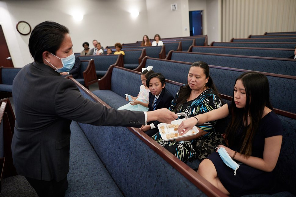 (Photo courtesy of The Church of Jesus Christ of Latter-day Saints) For demonstration purposes, a Utah congregation shows how family members could receive the sacrament tray while holding their face masks. The priesthood holder would follow COVID-19-recommended public guidelines by wearing a face mask and distributing the sacrament tray to each church member.