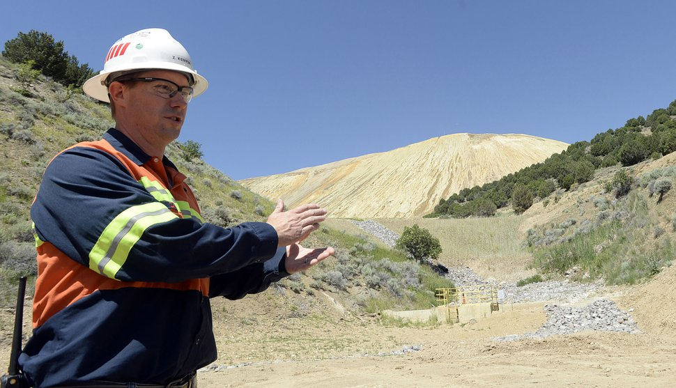 (Al Hartmann | Tribune File Photo) Zeb Kenyon, senior environmental advisor for Rio Tinto, points out the newly constructed waste dump and cut-off wall that stabilizes the bottom of the tailings pile and deals with runoff from large rain events on June 22, 2015.
