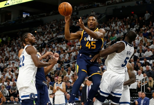 Utah Jazz's Donovan Mitchell, center, passes between Minnesota Timberwolves' Andrew Wiggins, left, and Gorgui Dieng, right, of Senegal, during the first half of an NBA basketball game Friday, Oct. 20, 2017, in Minneapolis. AP Photo/Jim Mone)