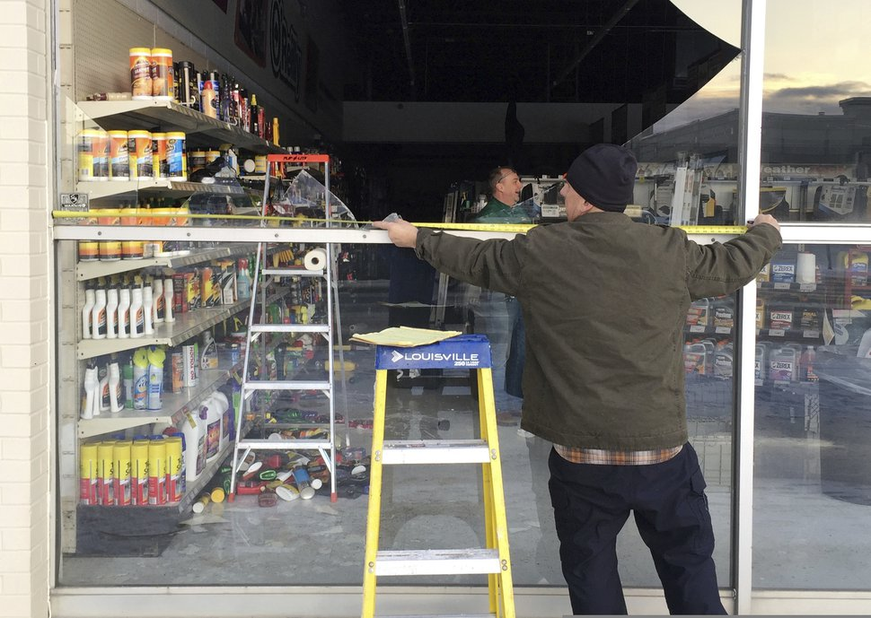 (Mike Dinneen | AP Photo) Dennis Keeling measures for a broken window at an auto parts store in Anchorage, on Friday, Nov. 30, 2018. Back-to-back earthquakes measuring 7.0 and 5.8 rocked buildings and buckled roads Friday morning in Anchorage, prompting people to run from their offices or seek shelter under office desks, while a tsunami warning had some seeking higher ground.