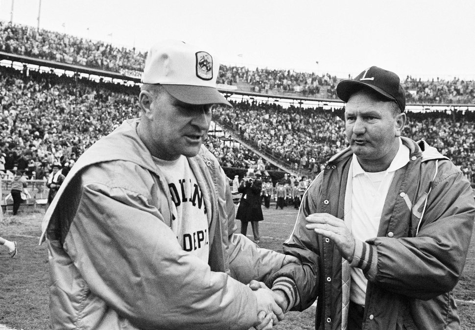 (AP Photo/File) In this Jan. 1, 1968, file photo, LSU coach Charlie McClendon, right, pats the hand of Wyoming coach Lloyd Eaton in the Sugar Bowl at New Orleans. Eaton died in 2007.