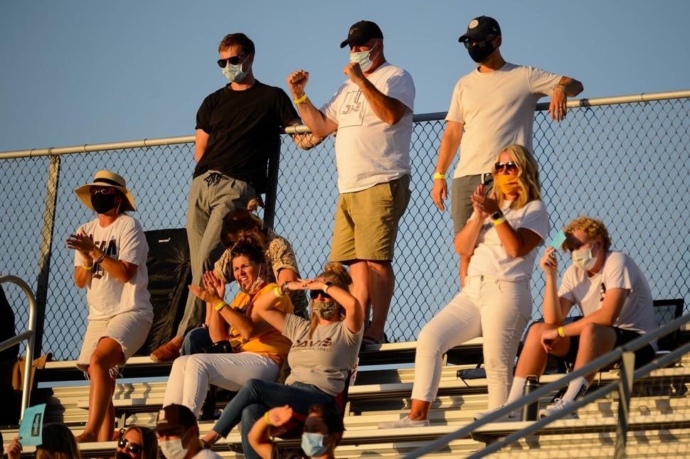(Trent Nelson | The Salt Lake Tribune) Masked Davis fans look on as Herriman hosts Davis High School football, in Herriman on Thursday, Aug. 13, 2020.