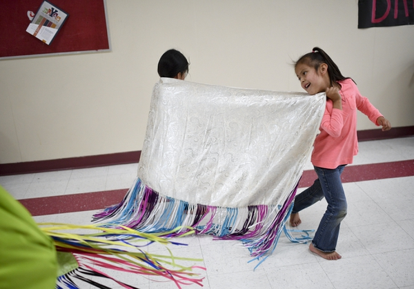 Phoebe Clark looks back as she runs away with a shawl during a dance class held by Alpine School District's Title VI American Indian Education program Wednesday, May 2, 2018, at Mountain View High School in Orem, Utah. The program aims to promote academic productivity in raising test scores and graduation rates. (Isaac Hale /The Daily Herald via AP)