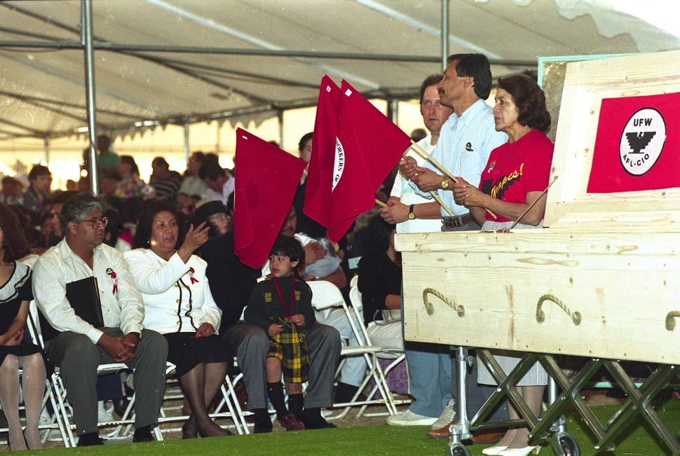 FILE - In this April 28, 1993, file photo, Dolores Huerta, right, holds a flag at the start of a rosary for United Farm Workers leader Cesar Chavez in Delano, Calif. Second from left and gesturing is Chavez' widow, Helen Chavez. Huerta, the social activist who formed a farm workers union with César Chávez and whose Si, Se Puede chant inspired Barack Obama's 2008 presidential campaign slogan, is the subject of a new PBS documentary. The film Dolores examines the life of the New Mexico-born Mexican-American reformer from her time as a tireless United Farm Workers leader and a campaign volunteer for Sen. Robert Kennedy's 1968 presidential run. (AP Photo/Eric Risberg, File)
