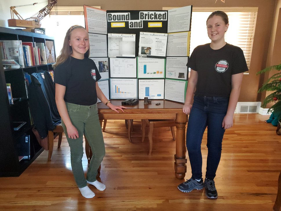 (Becky Jacobs   The Salt Lake Tribune) Sidor Clare, left, and Kassie Holt, right, stand next to their project board Oct. 21 in Sandy. The two were named among 30 finalists in a national science competition for their project focused on making building materials for Mars.