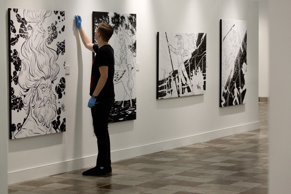 Taylor Wright, a gallery assistant, wipes down the wall in the gallery at the Woodbury Art Museum at University Place on Friday, July 27, 2018, in Orem, Utah. Wright was preparing the Heroes and Villians show. (Evan Cobb/The Daily Herald via AP)