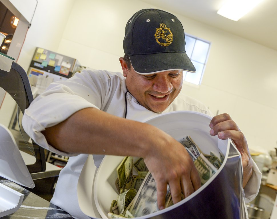 (Leah Hogsten | Tribune file photo) Adalberto Diaz Labrada, chef and owner of FIllings & Emulsions bakery in Salt Lake City, shows the cash collected during the 2018 Families Belong Together bake sale.