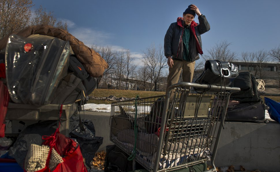 (Leah Hogsten | The Salt Lake Tribune) Ron Barrett is overwhelmed as he looks over the four shopping carts that contain his and his wife's belongings. Hours before, police officers told the homeless couple to move their tent and belongings two times during the night or risk getting another 'no camping' ticket. Ron's goal was to re-pack the tent they've been living in Salt Lake City, get organized and downsize for easier mobility, but sleep deprivation and anxiety from the night's events wore him down.