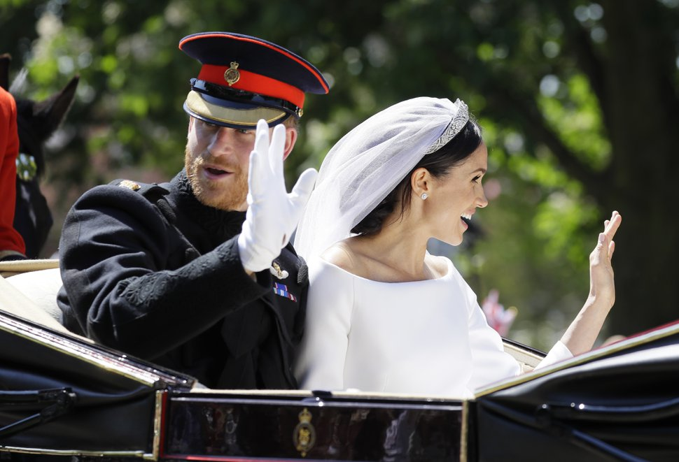 Britain's Prince Harry, left, and Meghan Markle wave from a carriage after their wedding ceremony at St. George's Chapel in Windsor Castle in Windsor, near London, England, Saturday, May 19, 2018. (AP Photo/Kirsty Wigglesworth, pool)