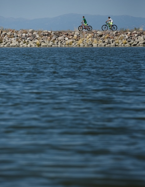 (Francisco Kjolseth | The Salt Lake Tribune) Kids ride their bikes around the popular Black Ridge Reservoir in Herriman on Tuesday, Aug. 28, 2018, where warning signs have been posted after an outbreak of algae-related toxin cyanobacteria was detected in the water.