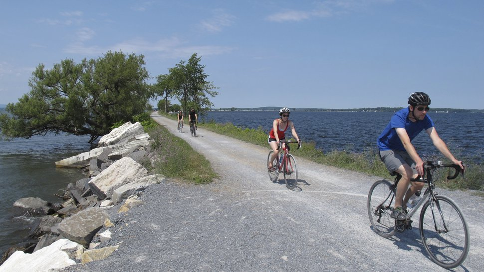 In this July 22, 2017 photo taken in Colchester, Vt., bicyclists ride on the Island Line Trail bike path on an abandoned railroad causeway from the Vermont mainland to the Lake Champlain islands. The seasonal ferry on the three-mile section of the Island Line Trail bike path carries cyclists across the opening in the causeway so they can reach the islands. (AP Photo/Wilson Ring)