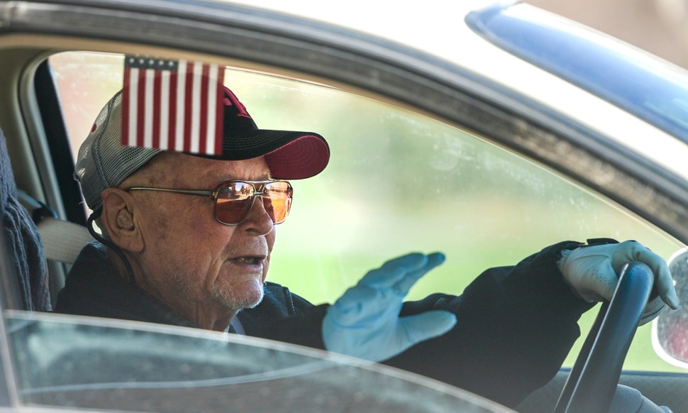 (Leah Hogsten | The Salt Lake Tribune) Millcreek Senior Center member Paul Baker waves to the staff and thanks them for his Friday lunch. Millcreek Senior Center hands out meals during the daily drive thru lunch service, Friday, March 27, 2020. All of Salt Lake County's senior centers have been closed indefinitely in order to protect a population that's thought to be more vulnerable to COVID-19.