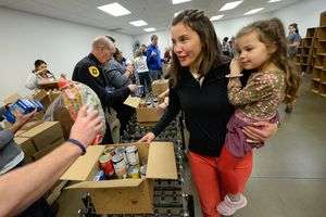 (Francisco Kjolseth  |  The Salt Lake Tribune) Salt Lake City Mayor Erin Mendenhall works the line with daughter Mila LaMalfa, 4, in tow as they volunteer at the Utah Food Bank for the Martin Luther King Jr. Day of Service on Monday, Jan. 20, 2020.