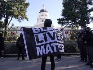 "(Rich Pedroncelli | AP photo)  A demonstrator holds a ""Black Lives Matter"" flag during a protest at the state Capitol in Sacramento, Calif., Wednesday, Jan. 20, 2021."