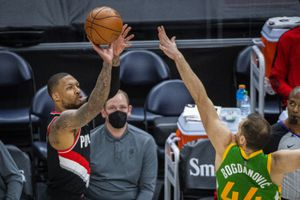 Portland Trail Blazers guard Damian Lillard (0) shoots a 3-pointer against Utah Jazz forward Bojan Bogdanovic (44) during the first half of an NBA basketball game Thursday, April 8, 2021, in Salt Lake City. (AP Photo/Isaac Hale)