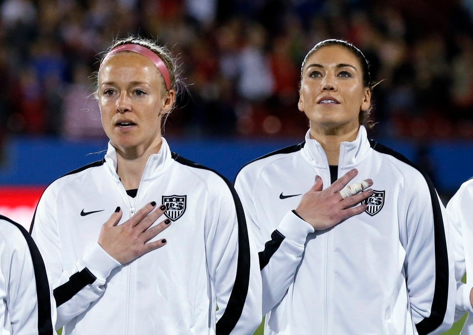 United States' Becky Sauerbrunn, left, and Hope Solo, right, stand during the playing of the national anthem before the team's CONCACAF Olympic qualifying tournament soccer match against Costa Rica on Wednesday, Feb. 10, 2016, in Frisco, Texas. (AP Photo/Tony Gutierrez)