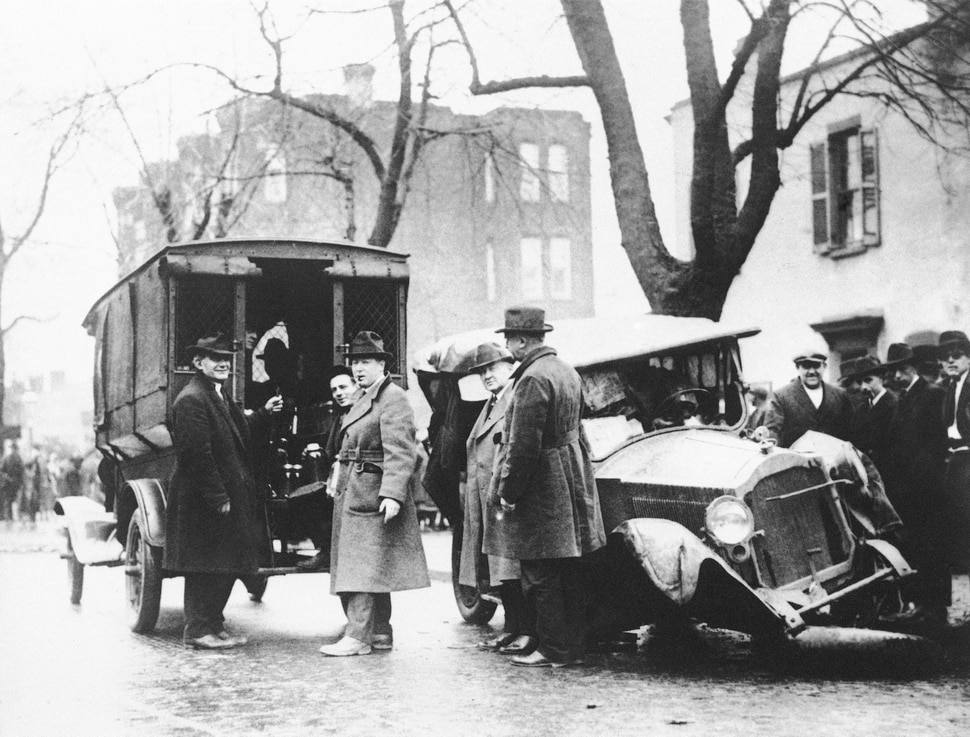 FILE - In this Jan. 23, 1922, file photo a patrol wagon filled with confiscated moonshine sits next to a wrecked car of bootleggers in Washington. Prohibition greatly expanded federal law enforcement powers and turned millions of Americans into scofflaws. It provided a new revenue stream for organized crime. (AP Photo, File)