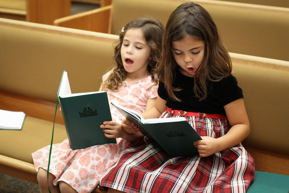 (Courtesy of the LDS Church) Two girls sing from a Latter-day Saint hymnbook.