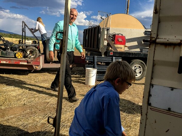 Trent Nelson | The Salt Lake Tribune Gabriel Owen, center, helps load a truck and trailer for members of the FLDS polygamous sect living outside of Beaver, Saturday July 15, 2017. Owen and the Davis County Cooperative Society have been offering service and donations to needy FLDS members who were evicted from UEP homes in Hildale and Colorado City, Ariz. Owen's children Kathrynn and Ammon are at left and right.