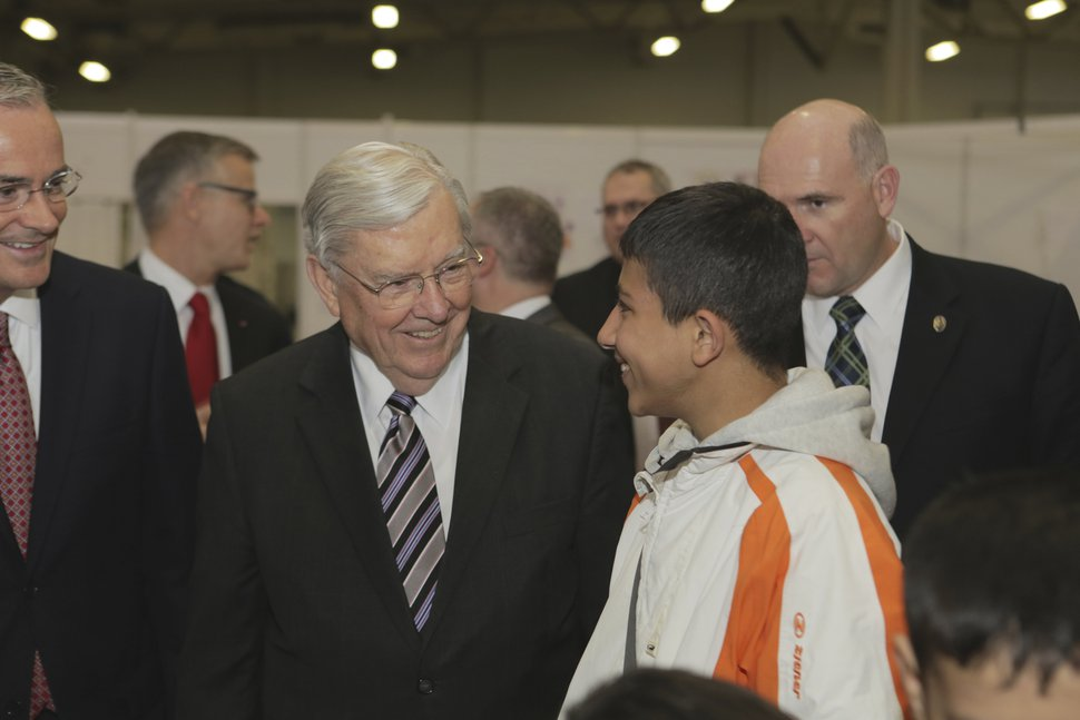 (Photo courtesy of The Church of Jesus Christ of Latter-day Saints) Apostle M. Russell Ballard visits with a young man at a refugee shelter in Berlin, Germany, in 2015.