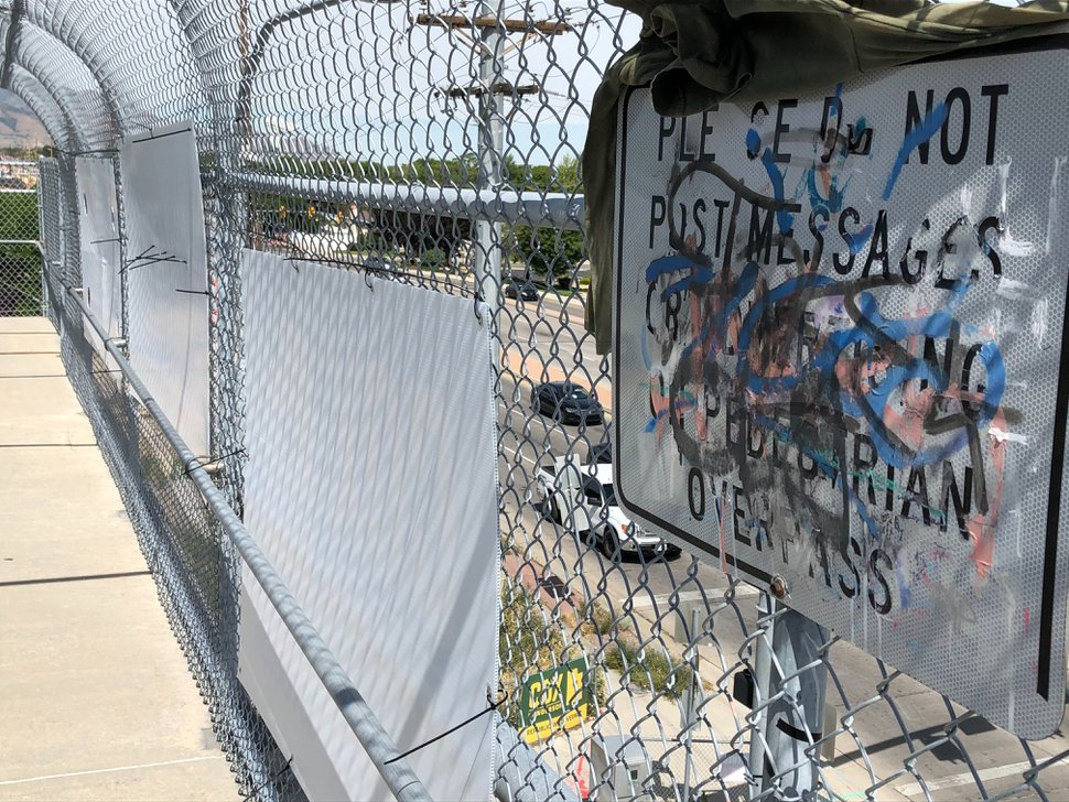 (Lee Davidson | The Salt Lake Tribune) Vandals painted over a state sign warning about a ban on hanging signs from a pedestrian overpass, while numerous campaign signs hang nearby on a bridge over Bangerter Highway at 4100 South on June 20, 2020.