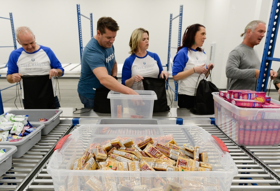 (Francisco Kjolseth | The Salt Lake Tribune) USANA staff volunteer their time assembling food bags for at-risk youth at the newly-renovated packing and storage facility next to the headquarters of the Salt Lake City company on Wed. Dec. 11, 2019. The USANA Foundation has acquired two local charities, Kids Next Door and KidsEat!, that provides hundreds of food bags every week for the kids for the weekends and during long school breaks.
