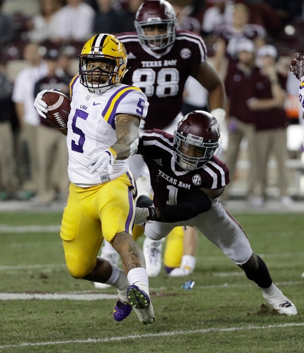 LSU running back Derrius Guice (5) breaks away from Texas A&M defensive back Nick Harvey (1) as he runs for a touchdown during the first quarter of an NCAA college football game Thursday, Nov. 24, 2016, in College Station, Texas. (AP Photo/David J. Phillip)