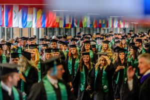 Trent Nelson  |  The Salt Lake Tribune Utah Valley University graduates walk through the school's Hall of Flags at the beginning of commencement in Orem, Thursday, April 28, 2016. UVU awarded 5,409 degrees at its 75th commencement.