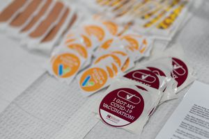 (Francisco Kjolseth | The Salt Lake Tribune) Retired oncology nurse Wendy Dewey lines up stickers and action hero bandaids as 12-15 year olds get their vaccinations against COVID-19 at the Mountain America Expo Center in Sandy on Tuesday, May 18, 2021.