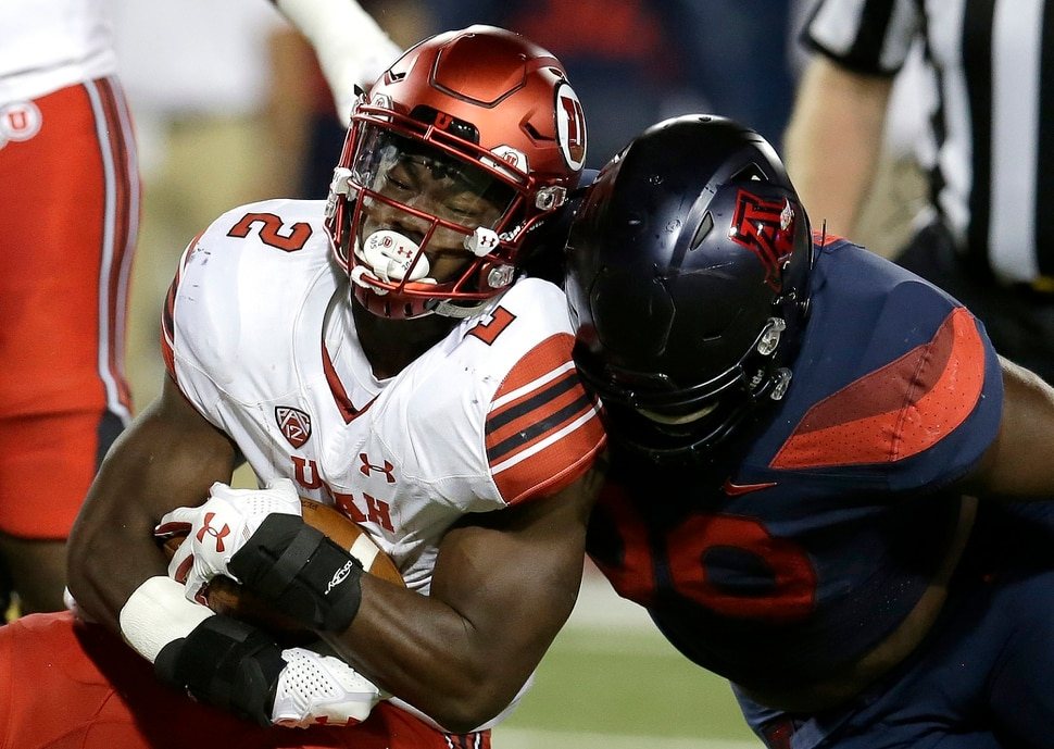 Utah running back Zack Moss (2) is tackled by Arizona defensive lineman Dereck Boles during the first half of an NCAA college football game, Friday, Sept. 22, 2017, in Tucson, Ariz. (AP Photo/Rick Scuteri)