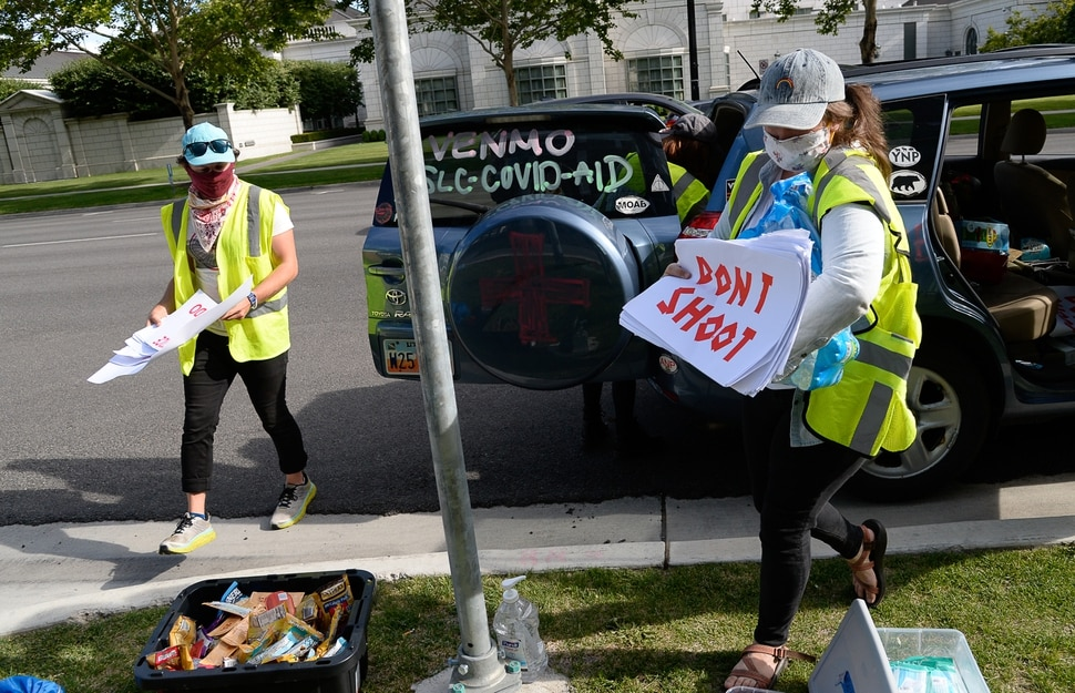 (Francisco Kjolseth | The Salt Lake Tribune) Isaac Pritt and Madalena McNeil work with the Salt Lake Valley Mutual Aid program, handing out water and administering first aid for demonstrators gathered at the Salt Lake County District Attorney's office for a Justice for Bernardo Palacios Rally, on Thursday, June 18, 2020.