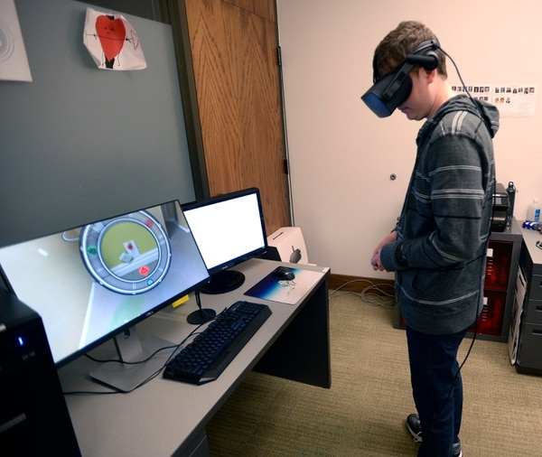 (Al Hartmann | The Salt Lake Tribune) Student engineer Alex Pedersen wears virtual reality goggles and runs through a simulation program for the College of Social Work at the University of Utah's Entertainment Arts and Engineering program. This simulation is to train social work students entering a home for a child well being interview to take in details of a family's life. Going room to room in the simulation participants look for details indicating a safe or unsafe home. Is there garbage in the kitchen? Are there liquor bottles and broken broken glass? Are there child safe toys and books present? They all provide clues to help make an assessment. He's focusing on a room detail on the monitor, left.