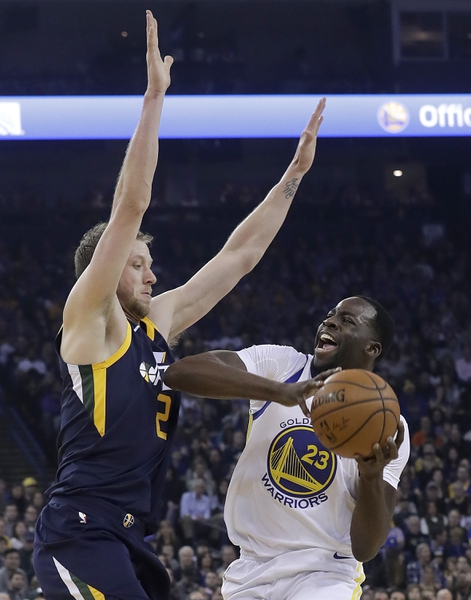 Golden State Warriors forward Draymond Green (23) is defended by Utah Jazz forward Joe Ingles during the first half of an NBA basketball game in Oakland, Calif., Wednesday, Dec. 27, 2017. (AP Photo/Jeff Chiu)