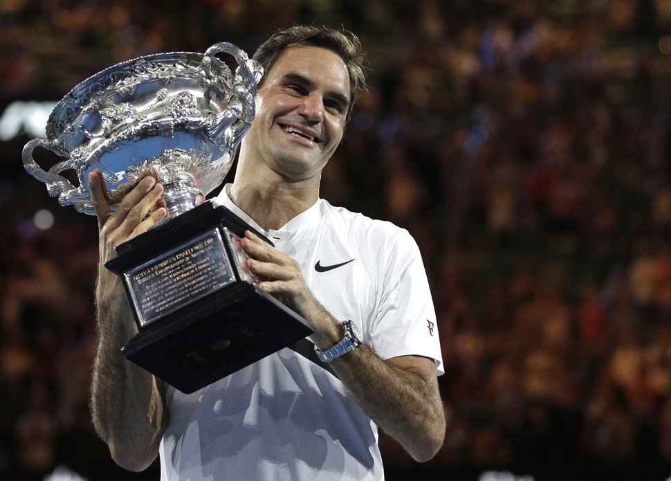 FILE - In this Jan. 28, 2018, file photo, Switzerland's Roger Federer holds his trophy after defeating Croatia's Marin Cilic during the men's singles final at the Australian Open tennis championships in Melbourne, Australia. Federer, who turns 37 in less than two months, seems to stay forever young. (AP Photo/Dita Alangkara, File)