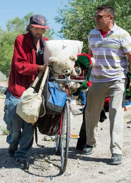 (Rick Egan | The Salt Lake Tribune) Jorge Mendez, Salt Lake County Health Department, assists Richard Smith with his belongings as the Health Department, Salt Lake City Police and other partners conduct a camp cleanup, Thursday, June 14, 2018.