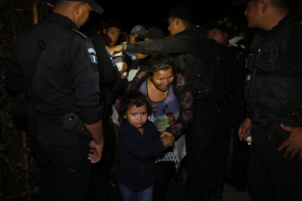 A Honduran migrant family walks between police officers as they enter Guatemala, at the border crossing in Agua Caliente, Tuesday, Jan. 15, 2019. The latest caravan of Honduran migrants hoping to reach the U.S. has crossed peacefully into Guatemala, under the watchful eyes of about 200 Guatemalan police and soldiers. (AP Photo/Moises Castillo)