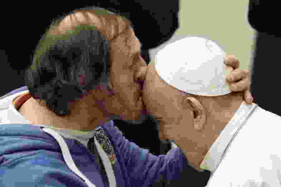 Pope Francis tenderly kissed on forehead by man in front-row seat