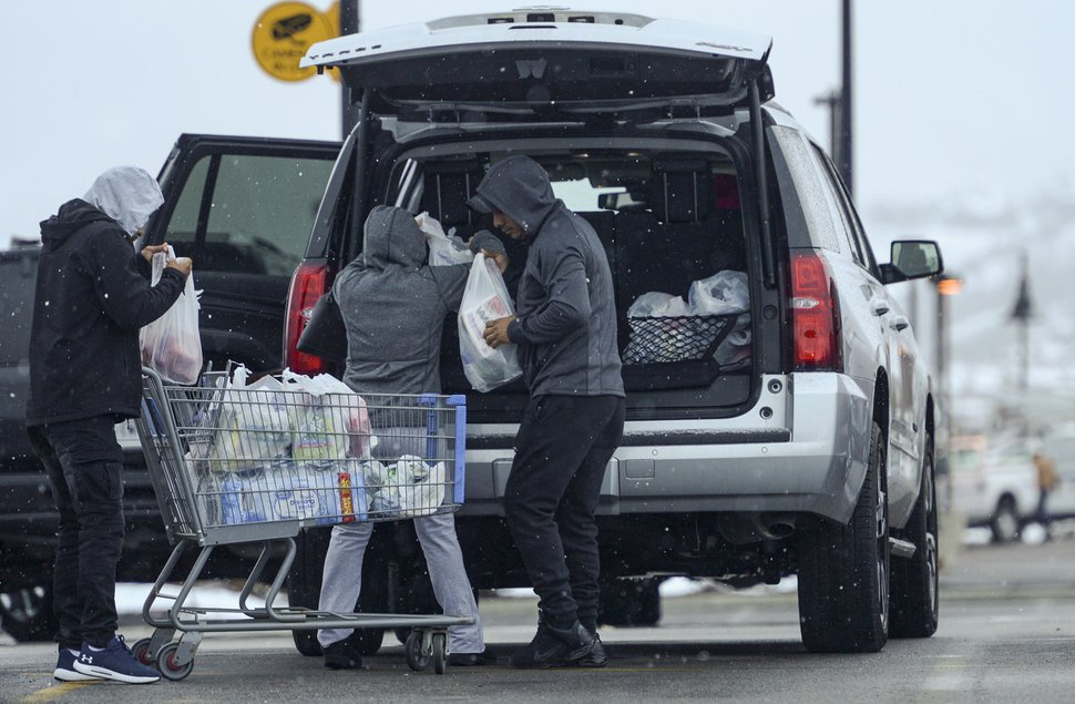 (Leah Hogsten | The Salt Lake Tribune) A family loads a cart full of groceries into their car outside of Walmart in Park City, March 25, 2020. Summit County issued a stay at home order on Wednesday, which goes into effect on Friday and lasts until at least May 1. The order, which is the first of its kind in Utah, asks residents to stop nonessential travel and orders nonessential businesses to close.