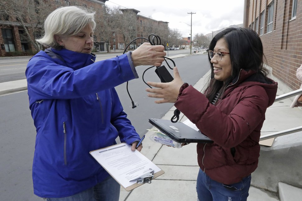 (Rick Bowmer | AP photo) English teacher Valerie Gates, left, distributes a computer to help with remote learning, to West High School junior Monserrat Roque at West High School Thursday, March 19, 2020, in Salt Lake City.