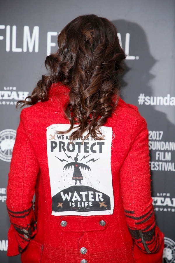 Actress Jennifer Beals shows a sign safety pinned on the back of her jacket protesting the Dakota Access Pipeline as she poses at the premiere of