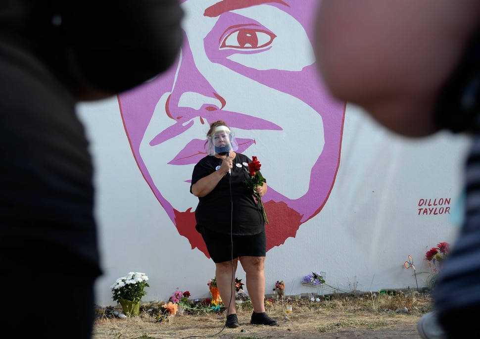 (Francisco Kjolseth | The Salt Lake Tribune) Gina Thayne, aunt of Dillon Taylor who raised him, speaks in front of his portrait as people gather for a vigil on the six-year anniversary of Taylor's death by the murals of people killed by police near 800 South and 300 West in Salt Lake City on Tuesday, August 11, 2020. Multiple families who's loved one's are depicted on the walls joined the vigil as they moved from portrait to portrait to remember them.