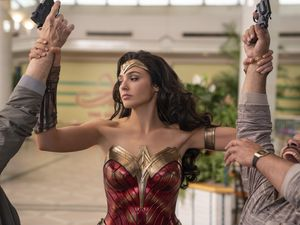 "(Clay Enos  |  courtesy of Warner Bros.) Wonder Woman, played by Gal Gadot, disarms a pair of thieves in an '80s shopping mall, in a scene from ""Wonder Woman 1984."" Five theaters along the Wasatch Front ranked in the top 10 nationally for ticket sales of the DC Comics-based superheroine action movie over Christmas weekend."