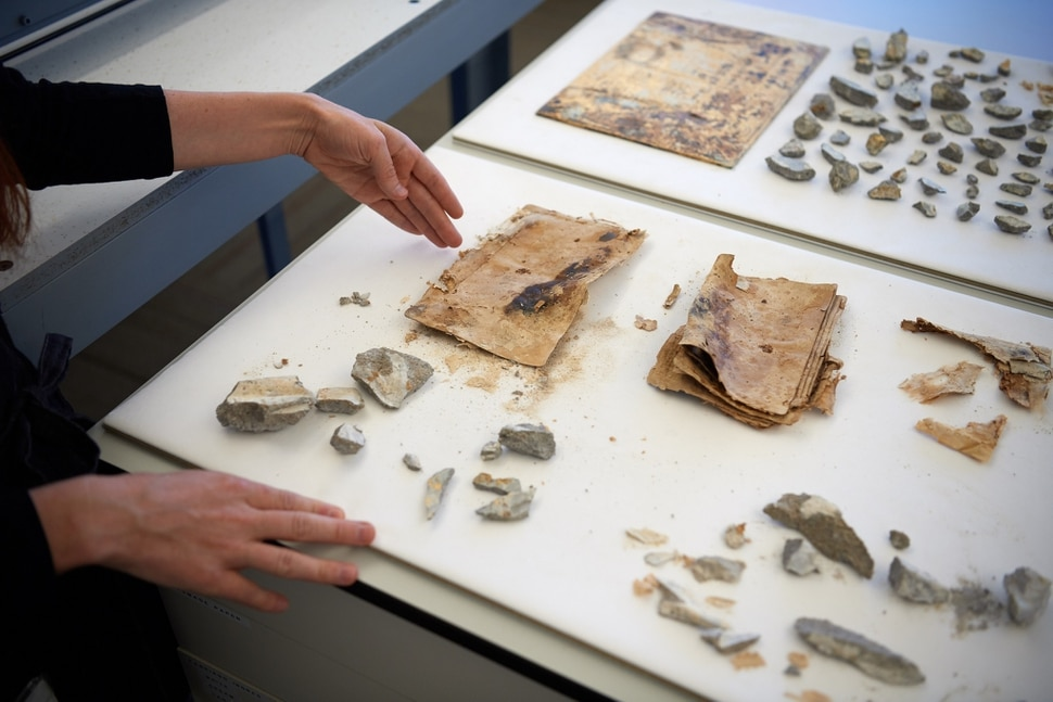 (Photo courtesy of The Church of Jesus Christ of Latter-day Saints) The items near the left hand in this shot are photos found in the capstone of the Salt Lake Temple. Newspapers in 1892 reported that the capstone contained photographs of Joseph and Hyrum Smith, Brigham Young, John Taylor, Wilford Woodruff, George Q. Cannon, Joseph F. Smith and the Salt Lake Temple. The photos are laminated together because of the moisture from the concrete that was trapped within the capstone. Thus, no photographic image remains.